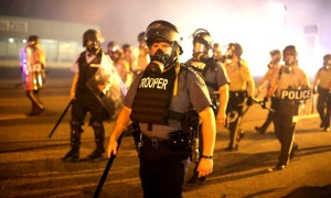 heavily-armed-police-advance-through-a-cloud-of-tear-gas-during-protests-in-ferguson-missouri