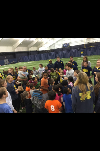 Student-athletes at an event where they teach kids through the YMCA their different sports and then play a group activity.